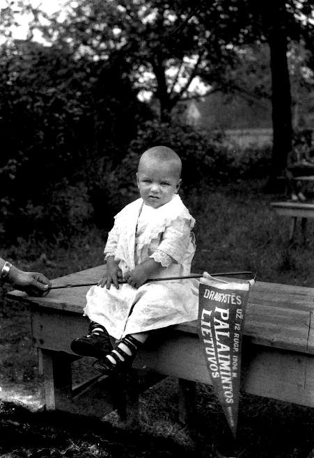 "Child with pennant which reads ""Friendship – 12 August 1906 – Blessed be Lithuania – Good Luck"